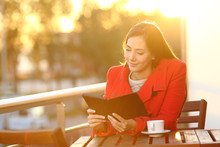 Woman Reading Ebook On A Balco...