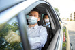 canvas print picture - health protection, safety and pandemic concept - male taxi driver wearing face protective medical mask driving car with passenger