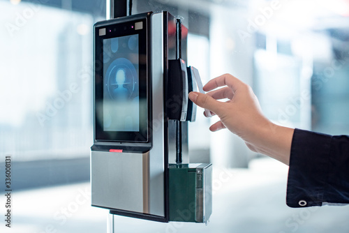Male hand using key card to open smart door lock for security system on glass door in office building Canvas Print