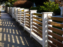 White Stucco Finished Fence Piers With Horizontal Brown Metal Slats. Front Yard With Light Modern Fence Along Sidewalk. Mediterranean Type Green Garden Background With Beautiful Front Yard.