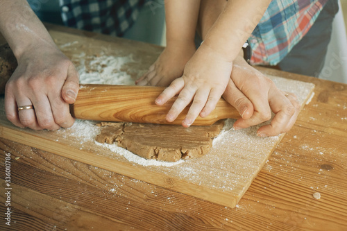 Mother teaches a child to roll a dough for biscuit with a rolling pin Fototapet