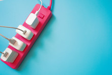 Top View Of White Mobile Charger Plugs Occupy On Pink Extension Power Strip On Light Blue PVC Texture Background ,enery Management And Save Electricity Power Technology Concept ,with Copy Space