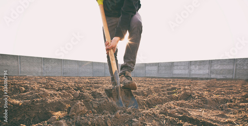 Fototapeta The man is digging the soil ground on his country house obraz