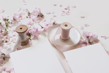 Wedding Spring Mockup Scene With Pink Blossoming Japanese Cherry Tree Branches, Petals And Silk Ribbons On Ceramic Plate. Closeup Of Blank Paper Greeting Cards On White Table Background.