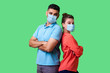 canvas print picture - Reliable friendship. Cheerful young couple of friends with surgical medical mask standing back to back with crossed hands and looking at camera . isolated on green background, indoor studio shot