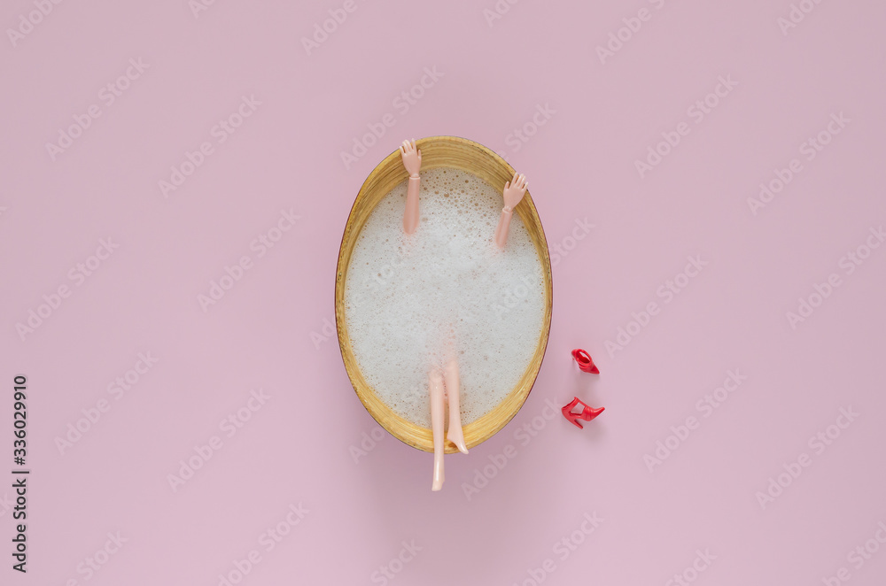 Fototapeta Doll bathing with bubble in wooden bathtub on pink background. Top view minimal beauty summer concept.