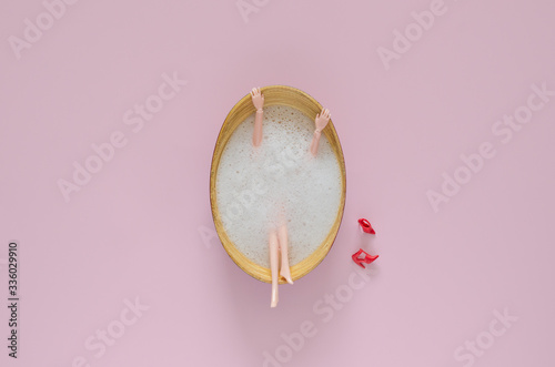 Obraz Doll bathing with bubble in wooden bathtub on pink background. Top view minimal beauty summer concept. - fototapety do salonu