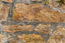 Kamienny Mur. Brazowe Kamienie.  Rosliny Na Murze. Mur Z Szarymi Spoinami.  Murowane Elementy Konstrukcyjne.  Tlo Do Zdjec. Chropowate , Zimne I Szorstkie Kamienie.
