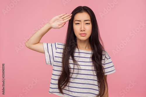 Yes sir! Responsible serious girl with brunette hair in striped t-shirt giving salute with attentive look, listening to command, ready to obey order Billede på lærred