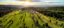 Aerial Landscape Panorama After Sunrise: Gorgeous Scenery With The Sun, Trees On Meadows Casting Long Shadows, Surrounded By Forests