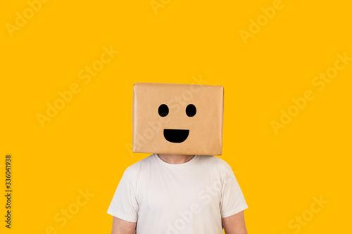 Fotomural Hombre con caja de cartón en la cabeza con una sonrisa en la cara sobre fondo amarillo liso brillante