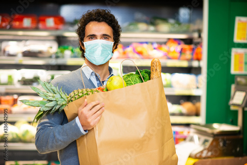 Fotografia Masked man holding an healthy food bag in supermarket during the coronavirus pan