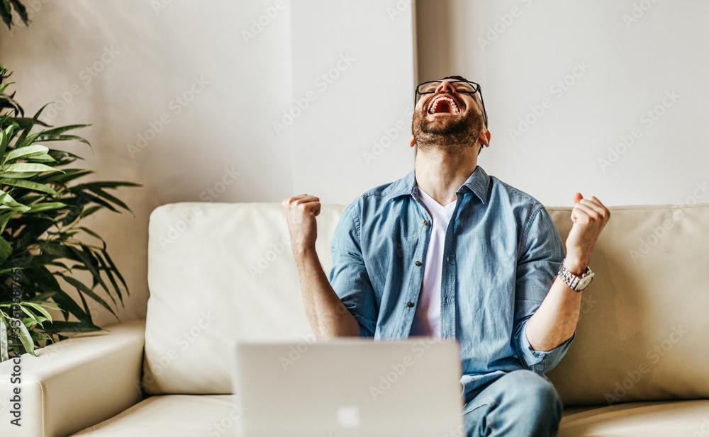 Fototapeta Excited male businessman celebrating victory, success, triumph  while working at laptop