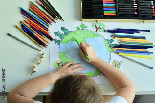 Child girl draws planet for earth day Canvas Print