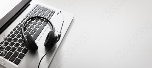 Fotografie, Obraz Headset on a laptop computer keyboard