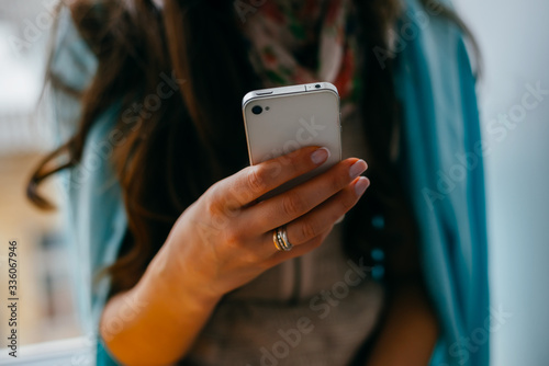 Fototapety, obrazy: Young woman dials number on mobile phone