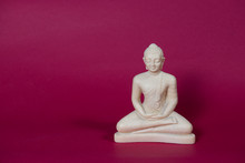 White Statue Of A Thai Buddha In Sitting Meditation On A Red Background