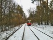 Tram going on rails in snowy winter forest