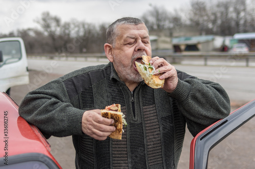 Portrait of Caucasian senior driver being delighted while gobbling lyulya kebab Canvas-taulu