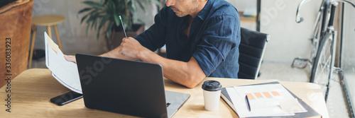 Valokuvatapetti Man working on laptop at bright studio