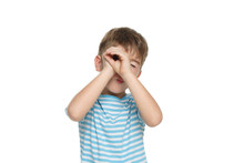 Little Funny Boy In A Blue Striped T-shirt Put His Hands To His Face While Portraying A Spyglass Isolated On A White Background.