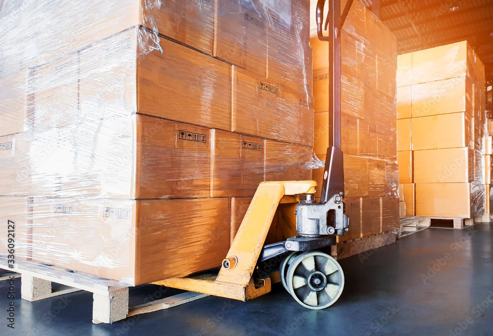 Fototapeta Interior of warehouse, close up hand pallet truck with stack package boxes on pallets, warehouse industry delivery shipment goods, logistics, transport