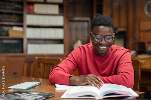 Happy university student reading in library Canvas