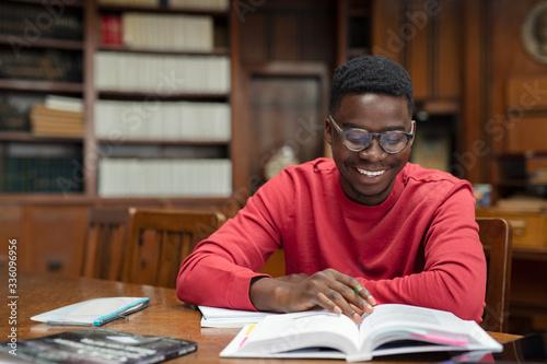 Obraz Happy university student reading in library - fototapety do salonu