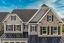 Aerial View Of Complex Facade With Stone Veneer Covered Gable 2 Jerkin Head Pitched Roof, Gray Horizontal Vinyl Siding, Dark Shutters On The White Frame Elegant Double Sash Windows Single Family Home