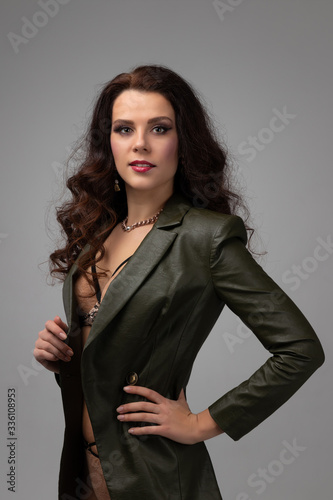 Attractive fashion model posing and smiling. Brunette with long curly hair on grey background. Concept of face care or hairstyling in salon