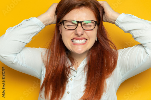 Valokuva Crazy angry young girl in glasses holds herself by the head on a yellow wall background