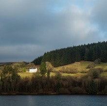 Beautiful Scenery Of Green Land With A Building By The Sea In Brecon Beacons National Park