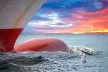 Dolphin Jumping Over Ship Prow On Red Sky Sunset
