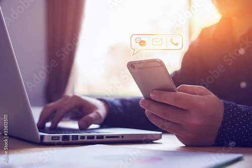 Fotografia Close up businessman using laptop holding mobile smart phone, using device to co