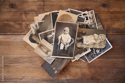 Tela old vintage monochrome photographs in sepia color are scattered on a wooden tabl