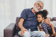 Grandfather Embraces Hug Love For The Little Girl Niece In A Warm Family Home.