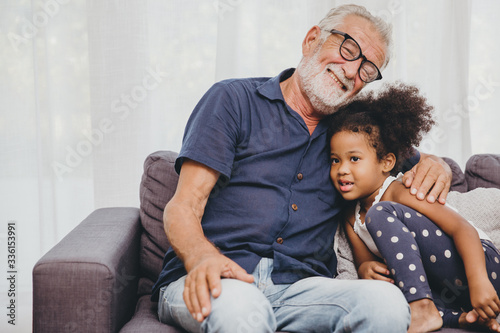 Fotografie, Tablou Grandfather embraces hug love for the little girl niece in a warm family home