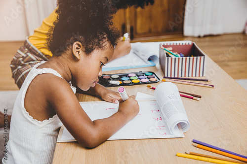 American Black preschool daughter kids doing homework learning education with her sister living together at home Fototapet