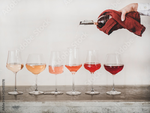 Fototapeta Shades of Rose wine in stemmed glasses placed in line from light to deep and womans hand pouring wine from bottle to glass, white wall background behind. Wine bar, wine shop, tasting concept obraz