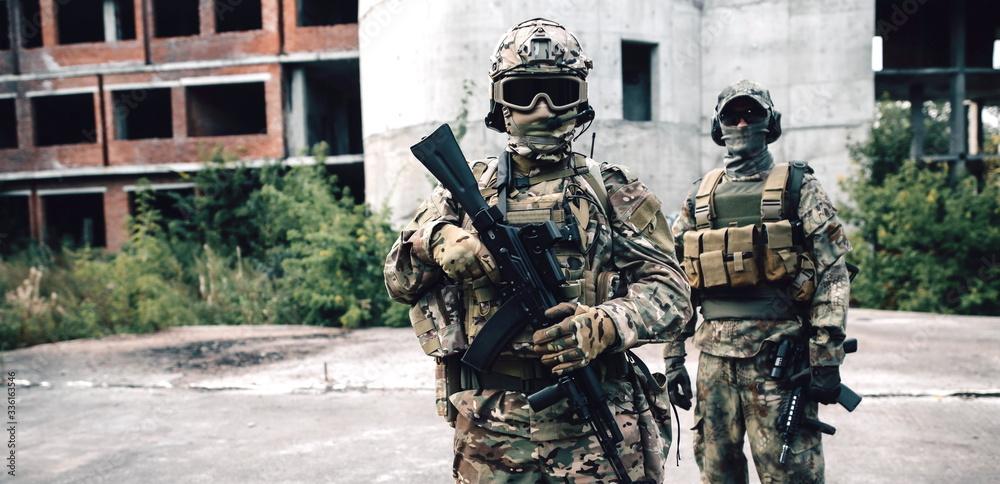 Fototapeta Portrait of two armed soldiers on a city street
