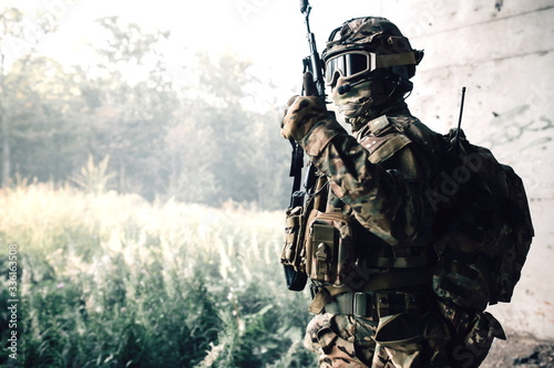 Obraz na plátně Camouflage soldier standing in a stone jungle with a rifle in his hands