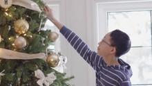 Boy Decorating Christmas Tree During Holidays