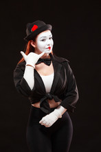 Portrait Of Female Mime Artist Performing, Isolated On Black Background. Woman Is Pretending Speaking By The Phone
