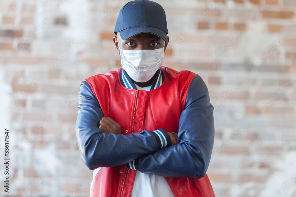 Fototapeta Handsome african man wearing medical mask is shocked with coronavirus 2019 danger on background of ruined red brick wall