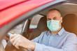 Senior mit Mundschutz beim Auto fahren in Covid-19 Pandemie
