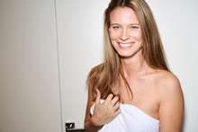 Portrait Of Smiling Young Woman Wrapped In Towel