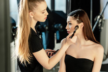 Young Makeup Artist Applying Face Powder On Attractive Model