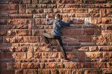 Woman Climbing On Sandstone Brick Wall