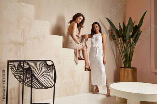 Two sexy beautiful woman friends brunette tanned skin makeup cosmetic fashion clothes summer collection cotton dress style summer journey walk date beach wear interior stairs leaves flowerpot.