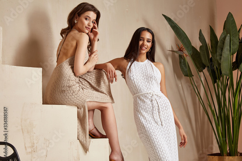 Fotografie, Tablou Two sexy beautiful woman friends brunette tanned skin makeup cosmetic fashion clothes summer collection cotton dress style summer journey walk date beach wear interior stairs leaves flowerpot